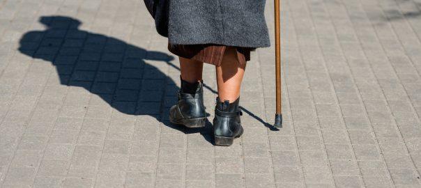 Eine alte Frau läuft die Straße entlang
